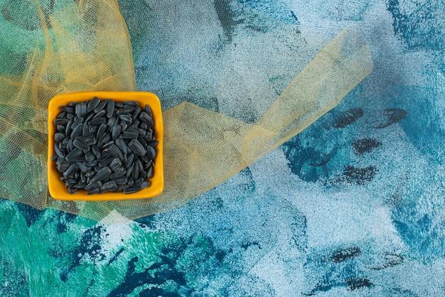 Ongeschilde zonnebloempitten in een kom op tule, op de blauwe tafel.