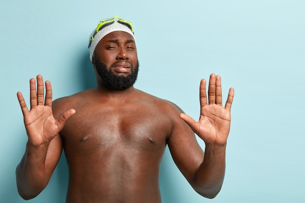 Ongeschoren afro-amerikaanse zwemmer man toont stop gebaar met afkeer, verwerpt iets, toont palmen op camera