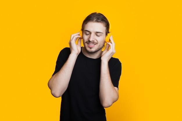 Ongeschoren blanke man met lang haar luistert naar muziek met een koptelefoon