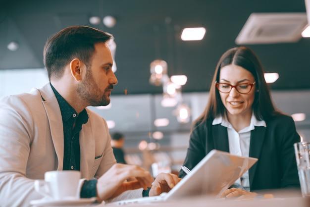Ongeschoren blanke zakenman met behulp van laptop en praten met zijn vrouwelijke collega zittend in cafetaria. wees de game-wisselaar.