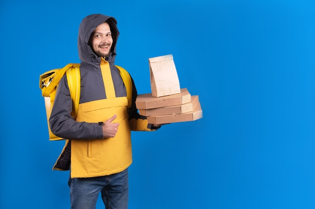 Ongeschoren donkerharige blanke koerier in geel windjack houdt een bestelling van pizza