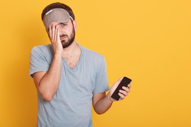 Ongeschoren donkerharige man kleedt slaapmasker, houdt smartphone in de hand en bedekt de helft van zijn gezicht met de handpalm, ziet er moe uit