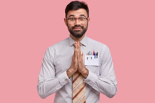 Ongeschoren jonge europese man met dikke haren, vraagt om hulp of belooft trouw te zijn, houdt de handpalmen tegen elkaar gedrukt, draagt een vierkante bril
