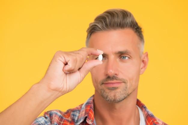 Ongeschoren man houdt vitaminepil vast, selectieve focus. geneeskunde concept. anabole en steroïden. levensmiddelenadditieven voor de gezondheid van mannen. bio vitamine complex. ziekte behandeling. product presenteren. man kijk naar drugs.