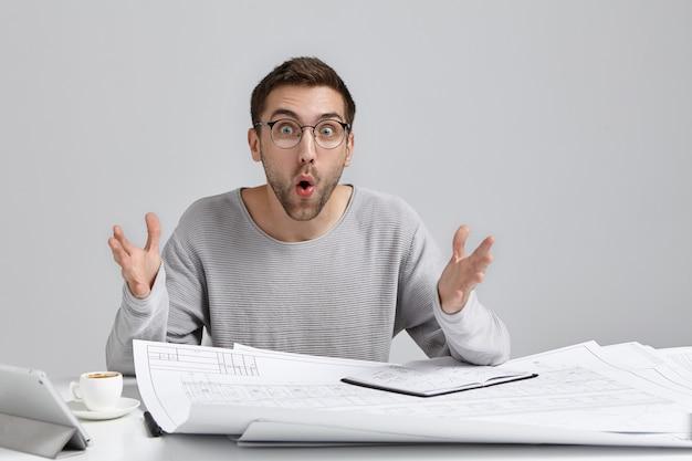 Ongeschoren verrast mannelijke ontwerper aan bureau, gebaren in geschokte uitdrukking, kijkt afgeluisterde ogen