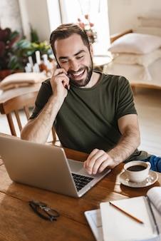 Ongeschoren volwassen man in casual kleding met behulp van laptop en smartphone tijdens het werken in flat