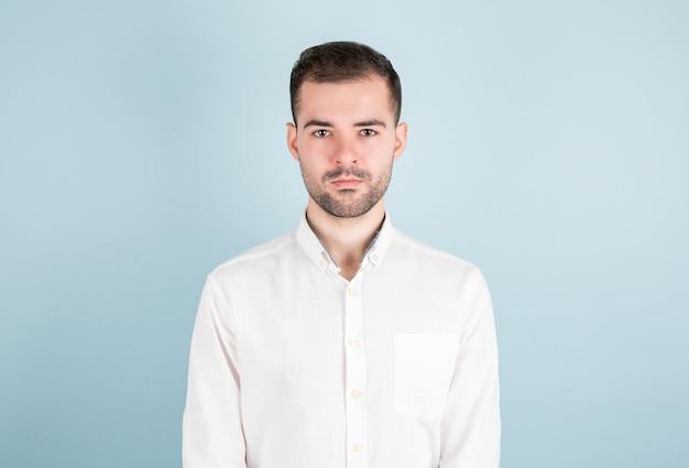 Ongeschoren zelfverzekerde ernstige jonge aantrekkelijke mannelijke zakenman die wit overhemd draagt