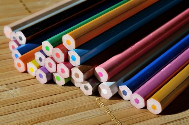 Ongeslepen kleurpotloden in een stapel op een houten ondergrond.