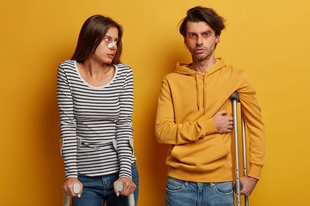 Ongeval vrouw en man lopen met krukken, hebben gezondheidsproblemen na een gevaarlijke rit op de motor, zijn roekeloze chauffeurs, komen naar de dokter voor consultatie, staan binnen over gele muur