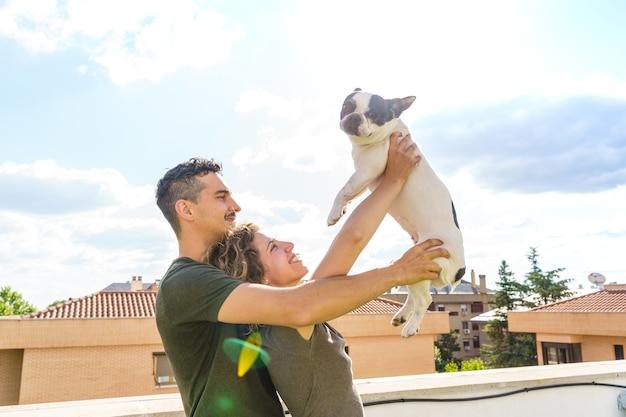 Ongewone familie met bulldog buitenshuis. horizontale weergave van paar spelen met huisdier thuis.