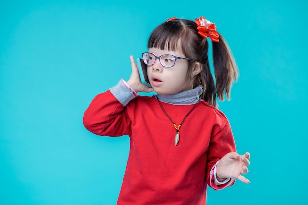 Ongewone gezichtskenmerken. buitengewoon klein kind in rode hoodie met het syndroom van down praten over smartphone
