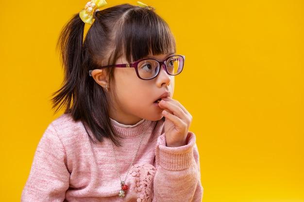 Ongewone gezichtskenmerken. nadenkend donkerharig kind met abnormaliteit die snacks eet terwijl hij gekleed is in een roze warme trui