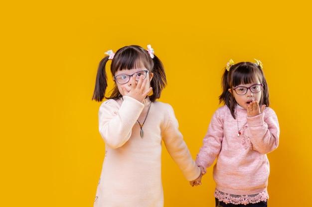Ongewone gezichtskenmerken. schattige jonge zussen met twee funky staarten op het hoofd terwijl ze poseren voor het fotograferen