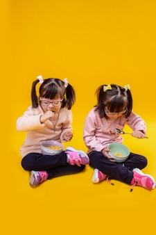 Ongewone kinderen met donker haar. gerichte kleine meisjes met een psychische stoornis die granen eten met melk uit diepe kommen