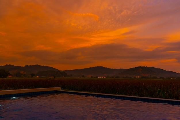 Ongewone oranje vurige zonsondergang in de tropen. uitzicht vanaf het zwembad naar een rijstveld en bergen