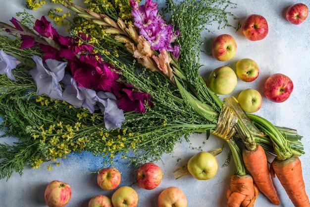 Ongewoon boeket van gladiolenbloemen met veldplanten en wortelen