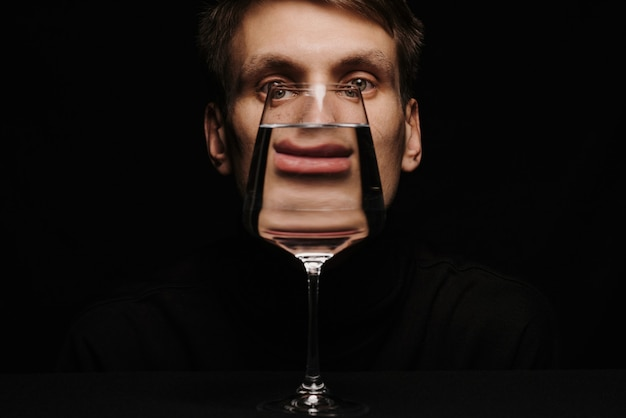 Ongewoon portret van een man die door een glas water kijkt op een donkere achtergrond