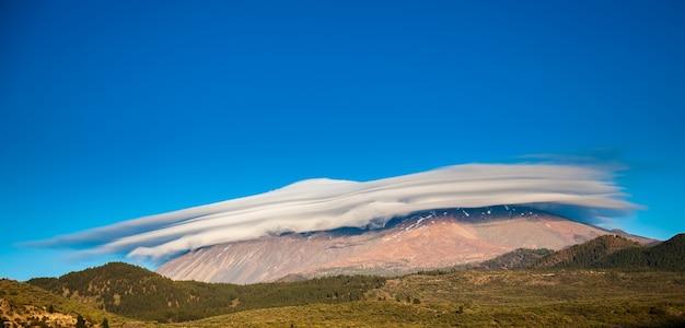 Ongewoon uitzicht op de berg teide bedekt met de hoed van wolken, tenerife, spanje