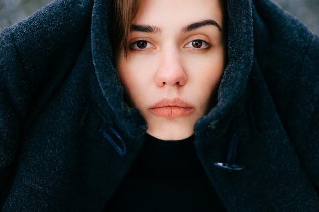 Ongewoon vrouwelijk portret. uniek expressief gezicht van de persoonsclose-up. jong ernstig meisje in de winter openlucht. vreemde bizarre vrouw met knal op voorhoofd. jas op het hoofd. hoofdtooi