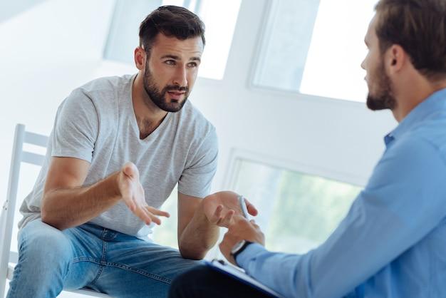 Ongezellig humeurige jongeman die naar zijn therapeut kijkt en om advies vraagt terwijl hij op zoek is naar een oplossing voor zijn problemen