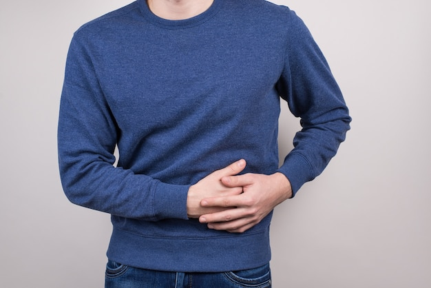 Ongezond eten voedingsconcept. bijgesneden close-up van ongelukkig trieste man aanraken linkerkant gevoel ernstige pijn geïsoleerde grijze muur