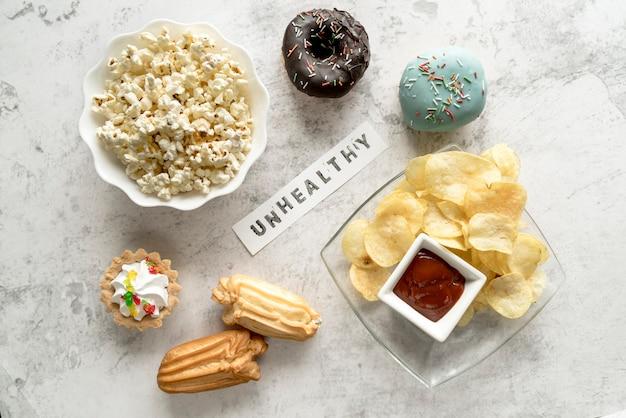 Ongezond tekst omgeven door smakelijke ongezond voedsel op concrete achtergrond