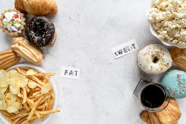 Ongezond voedsel op geweven achtergrond met vet en zoet woord