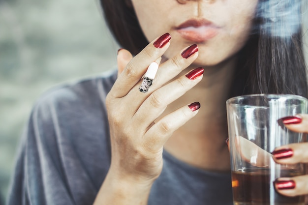 Ongezonde aziatische vrouw roken en alcohol drinken