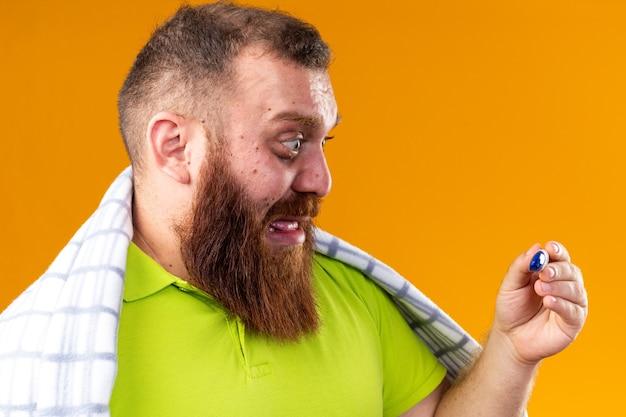 Ongezonde bebaarde man gewikkeld in een deken die zich ziek voelt en lijdt aan kou die de temperatuur controleert met behulp van een thermometer die gestrest en nerveus over de oranje muur staat