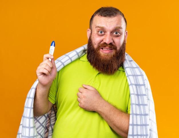 Ongezonde bebaarde man gewikkeld in een deken die zich ziek voelt en lijdt aan koude controle van de temperatuur met behulp van een thermometer die bezorgd en verward over de oranje muur staat