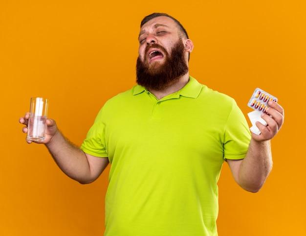 Ongezonde bebaarde man in geel poloshirt met glas water en pillen die zich vreselijk voelen en lijden aan koud huilen hard over oranje muur staan