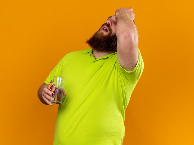 Ongezonde bebaarde man in geel poloshirt met glas water en pillen die zich vreselijk voelen lijden aan koude koorts en sterke hoofdpijn die over oranje muur staat