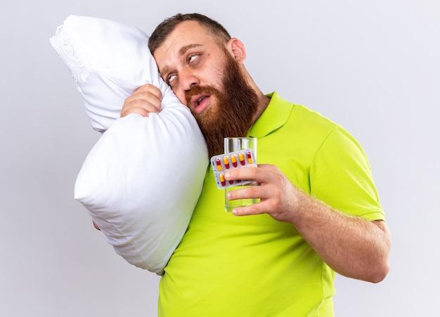 Ongezonde bebaarde man in geel poloshirt met kussen met glas water en pillen ziek voelen lijden aan griep staande over witte muur