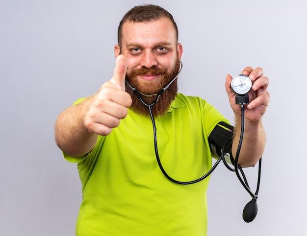 Ongezonde bebaarde man in geel poloshirt voelt zich beter bloeddruk meten met behulp van tonometer glimlachend duimen opdagen staande over witte muur