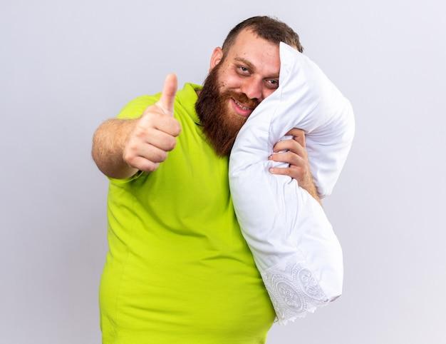 Ongezonde bebaarde man in geel poloshirt voelt zich beter terwijl hij een kussen vasthoudt terwijl hij glimlacht en zijn duimen omhoog laat staan terwijl hij over een witte muur staat
