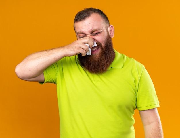 Ongezonde bebaarde man in geel poloshirt voelt zich verschrikkelijk en lijdt aan kou die zijn loopneus afveegt