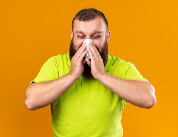 Ongezonde bebaarde man in geel poloshirt voelt zich verschrikkelijk en lijdt aan koud niezen in weefsel dat zijn loopneus snuit