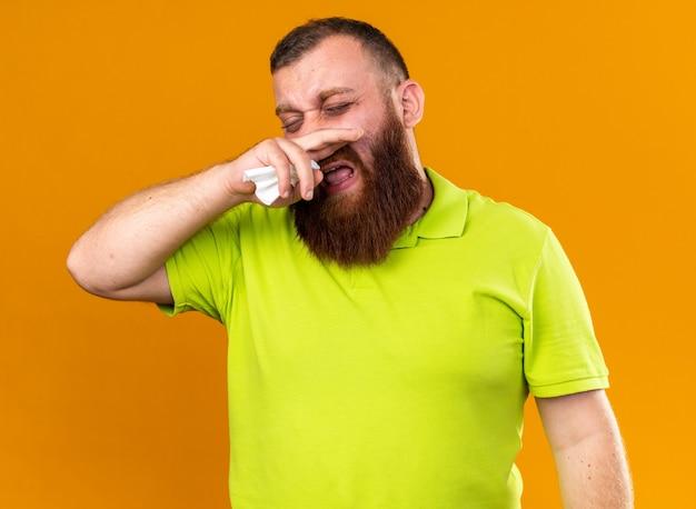 Ongezonde bebaarde man in geel poloshirt voelt zich vreselijk en lijdt aan kou die zijn loopneus afveegt die over oranje muur staat