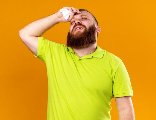 Ongezonde bebaarde man in geel poloshirt voelt zich vreselijk en lijdt aan verkoudheid met koorts met de hand op zijn voorhoofd die over de oranje muur staat