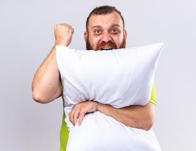 Ongezonde bebaarde man in geel poloshirt voelt zich ziek en knuffelt kussen met boos gezicht dat vuist over witte muur opheft