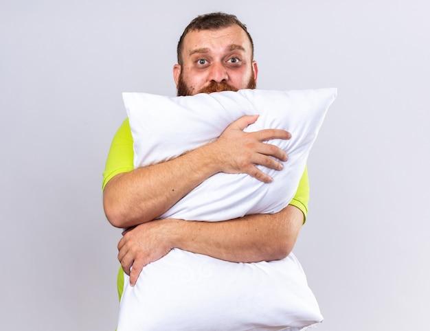 Ongezonde bebaarde man in geel poloshirt voelt zich ziek en knuffelt kussen met droevige uitdrukking die over een witte muur staat