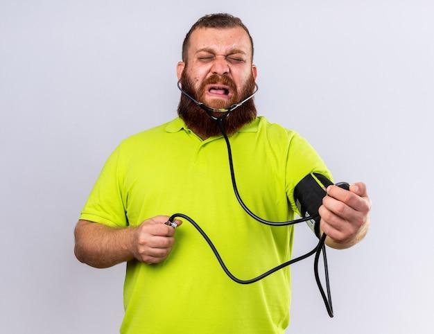 Ongezonde, bebaarde man in geel poloshirt voelt zich ziek om bloeddruk te meten met behulp van tonometer die er boos uitziet terwijl hij over een witte muur staat