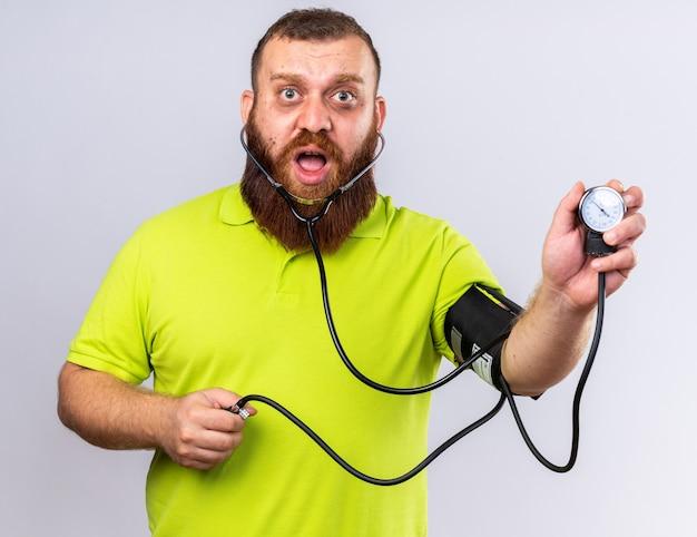Ongezonde, bebaarde man in geel poloshirt voelt zich ziek om bloeddruk te meten met behulp van tonometer en kijkt bezorgd over een witte muur