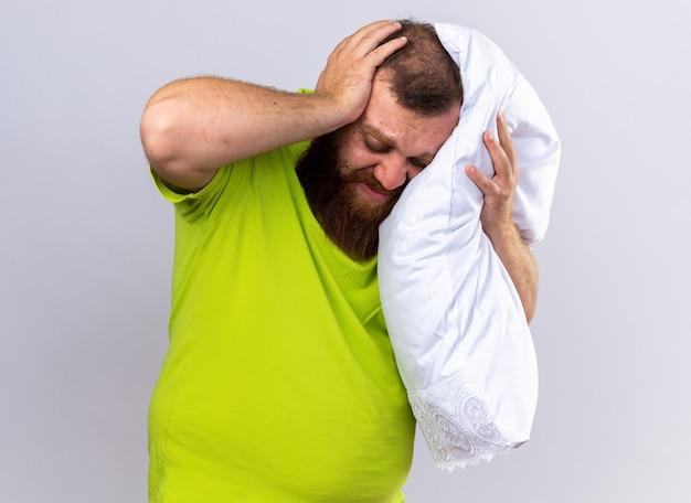 Ongezonde bebaarde man in geel poloshirt voelt zich ziek terwijl hij een kussen vasthoudt met sterke hoofdpijn die over een witte muur staat