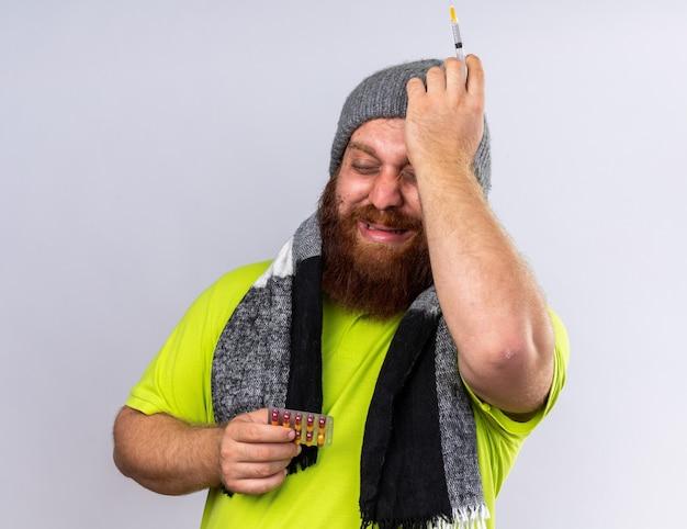 Ongezonde bebaarde man in hoed en met warme sjaal om nek ziek voelen lijden aan griep met spuit en pillen die verward over witte muur staan