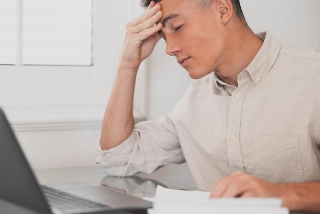 Ongezonde gestresste jongeman die thuis hoofdpijn heeft omdat hij overwerkt en hard studeert voor examens. moe mannelijke tiener huiswerk voor school