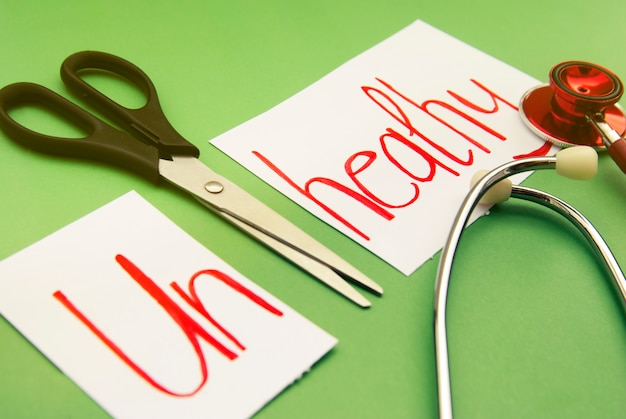 Ongezonde inscriptie. stethoscoop en schaar op groen. handgeschreven rode inscriptie. geneeskunde en gezond.