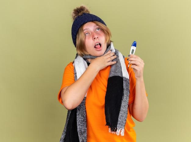 Ongezonde jonge vrouw die hoed met sjaal om haar hals draagt