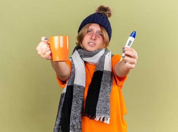 Ongezonde jonge vrouw die hoed met sjaal om haar nek draagt en zich onwel voelt het drinken van hete thee met digitale thermometer die lijdt aan griep en koorts die zich over de groene muur bevindt