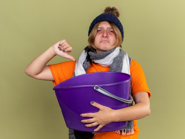 Ongezonde jonge vrouw die hoed met sjaal om haar nek draagt en zich ziek voelt en lijdt aan misselijkheid met bekken met duimen naar beneden staande over groene muur